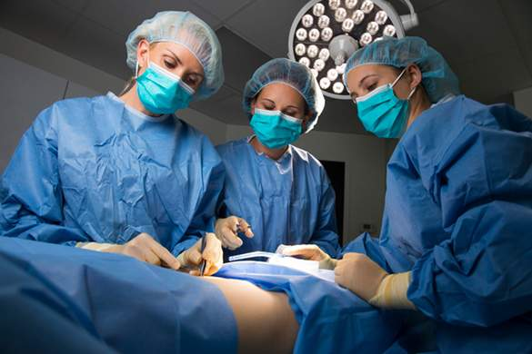Three of Our Staff in Scrubs During Operation