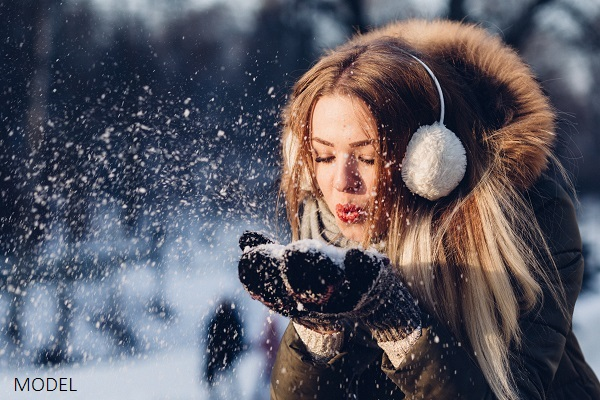 Woman blowing snow from her cupped hands